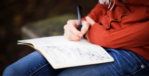 image of Cate Lycurgus sitting writing in a notebook